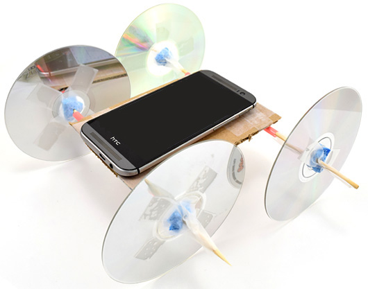 A smartphone rests on a vehicle with CD's as wheels