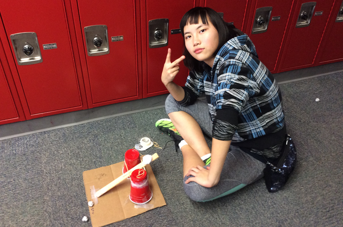 A student next to a ball launcher made from plastic cups, pencils, a ruler and tape