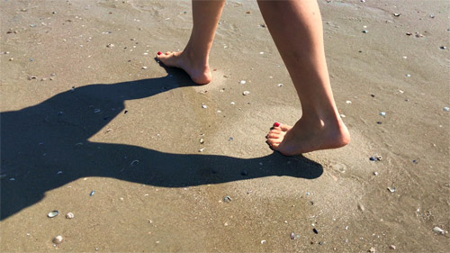 Close up photo of two feet walking across wet sand