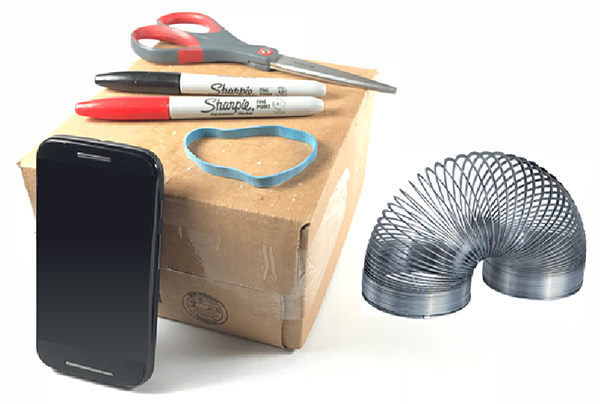 A smartphone, cardboard box, rubber band, scissors, two sharpies and a slinky