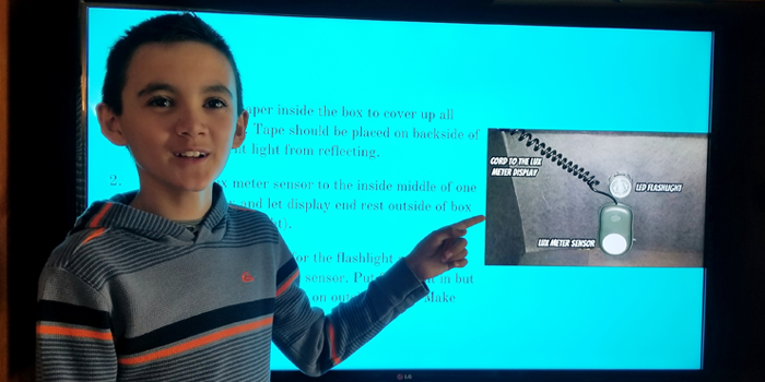 A students points to an image on a PowerPoint presentation projected behind him