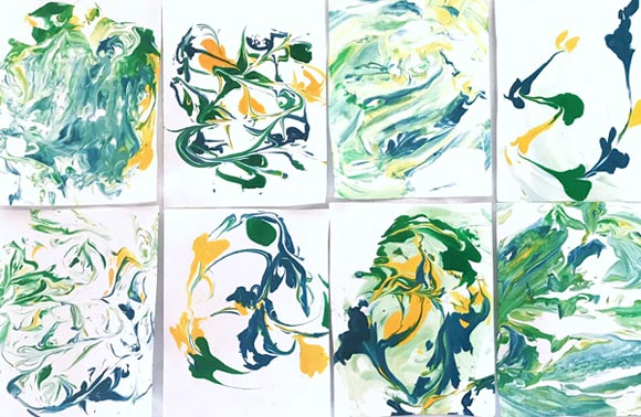 Eight different patterns of green, yellow and blue streaks create a marbling effect on various pieces of paper