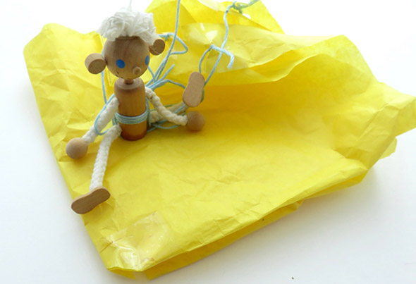 A wooden doll with a string harness and a tissue paper parachute