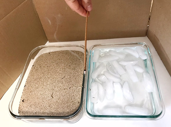 An incense stick is held between two containers filled with sand and ice water