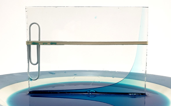 Blue liquid moves up the right side of two glass panes that are pressed together