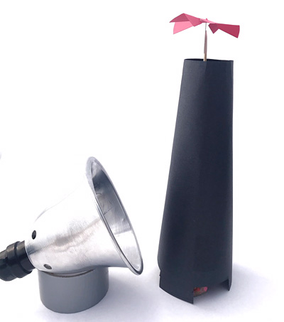 A small lamp next to a homemade updraft tower