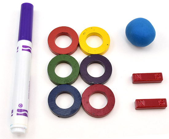 A marker, six magnetic rings, two bar magnets, and a ball of putty