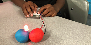 A child assembles a circuit made from an LED, battery pack and two balls of conductive play dough