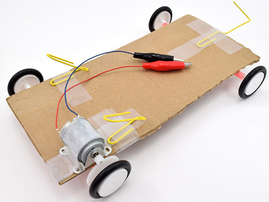Three paper clips are bent and taped to a solar powered car chassis to help support a solar panel placed above it