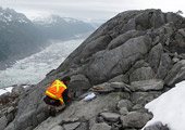 USGS geologist gathering data from glacier samples of granitic bedrock  in the Neacola Mountains of Alaska.