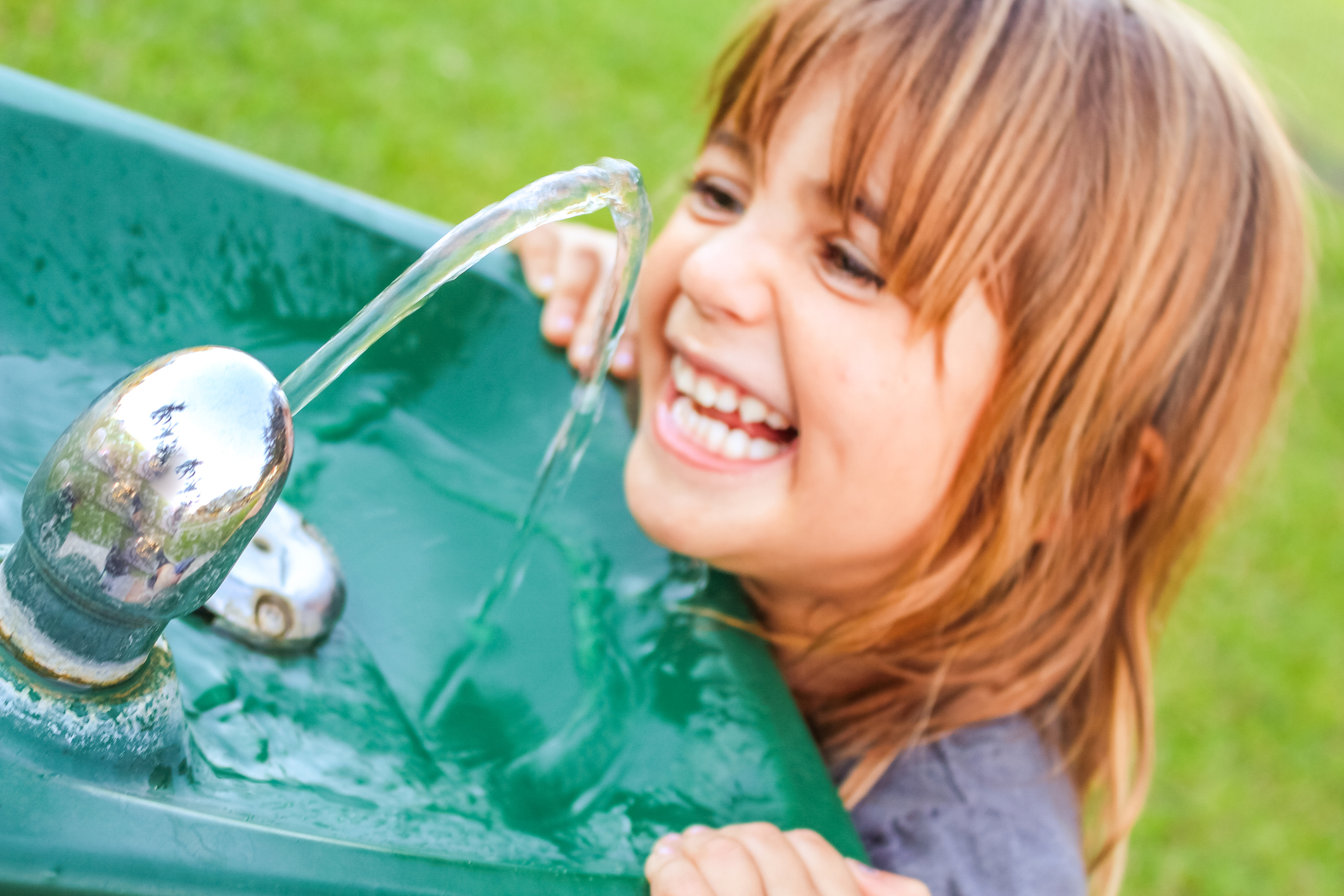 young girl using public drinking fountain
