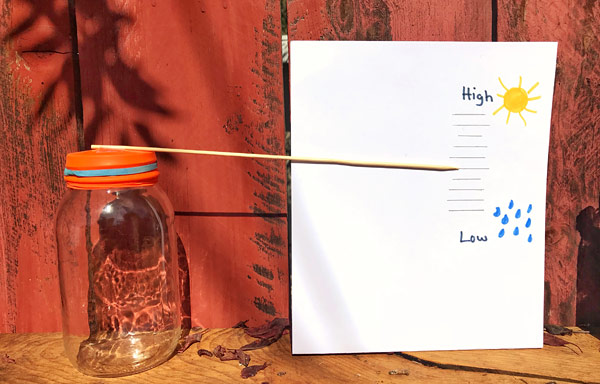 A glass jar, balloon, rubber band, and wooden skewer act as a modemade barometer