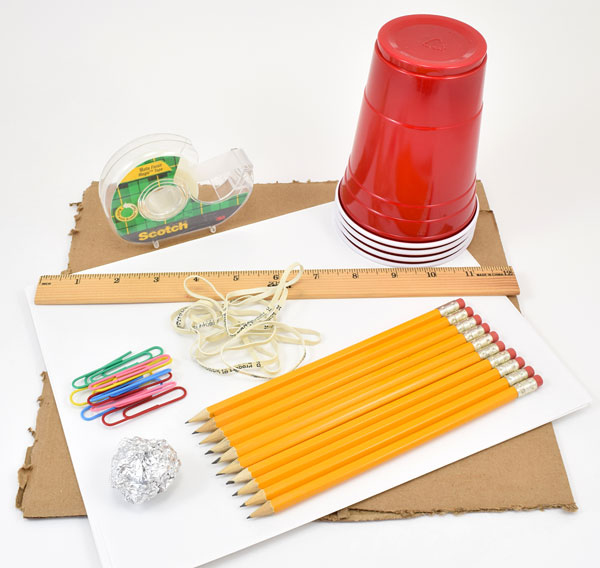Tape, plastic cups, a ruler, rubber bands, paperclips, pencils, a sheet of cardboard and a ball of aluminum foil