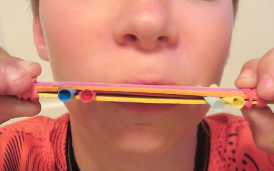 Homemade harmonica made from popsicle sticks, straws and rubber bands
