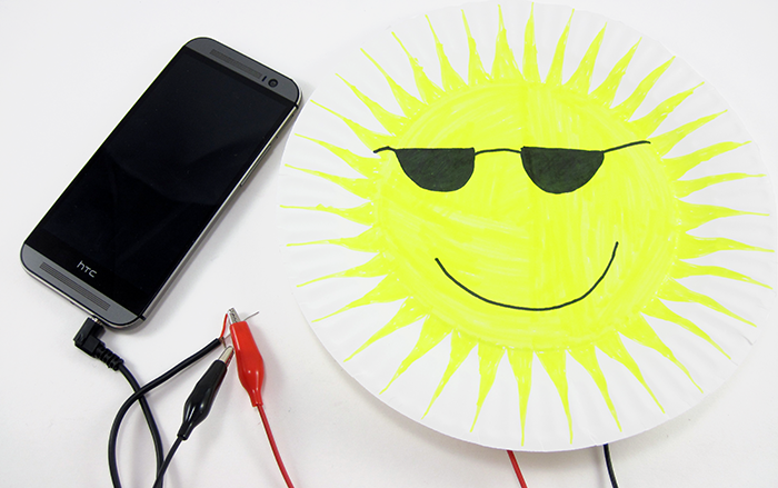 A decorated paper speaker connected to the audio jack of a smartphone