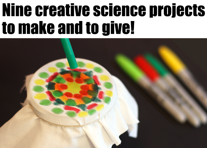 A cloth decorated with colorful ink dots is stretched over a cup and held with a rubber band