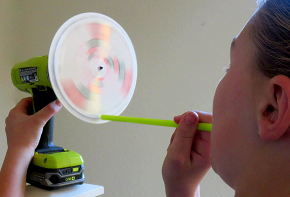 Girl operating the disk siren created in this science activity.