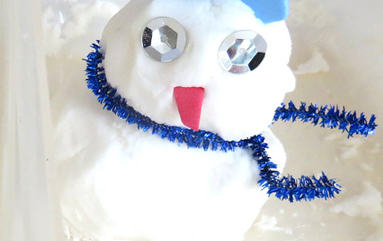 Picture of a snowman created with the foaming white snow of this science activity.
