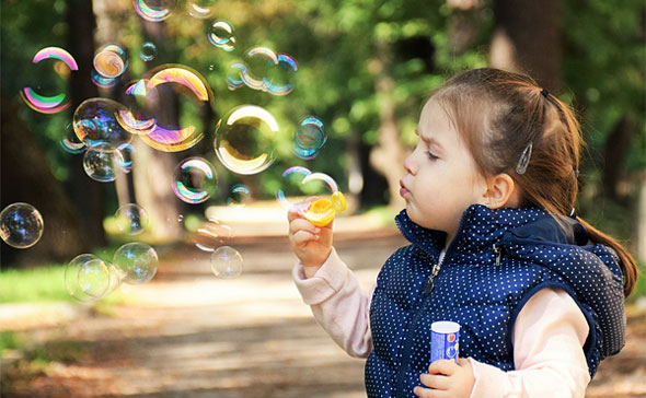 girl blowing bubbles in this science activity