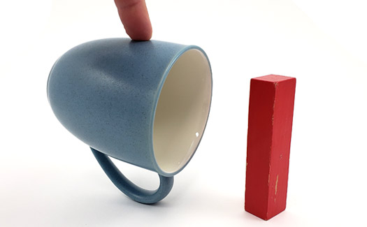 A wooden block balanced on one end, and a coffee mug precariously balanced on its handle.