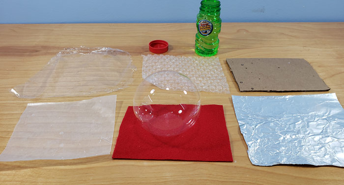Squares of materials arranged on a table next to a bottle of bubble solution, with a bubble resting on one of the materials.