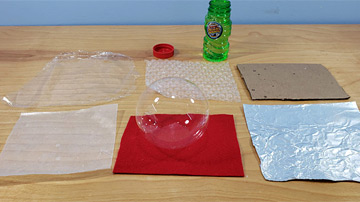 A soap bubble rests on a square sheet of red felt next to square sheets of other materials