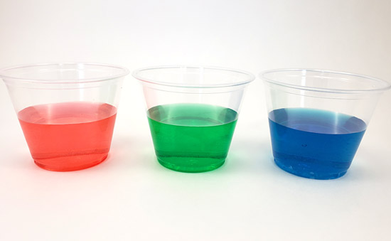 Three drinking glasses with red, green, and blue liquid in them.