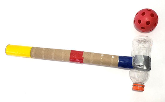 A whiffle ball next to a mallet made of a plastic bottle, tape and cardboard tubes