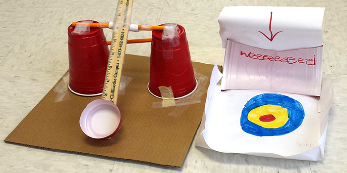 A ball launcher made from a ruler, pencils, tape and plastic cups next to a paper target