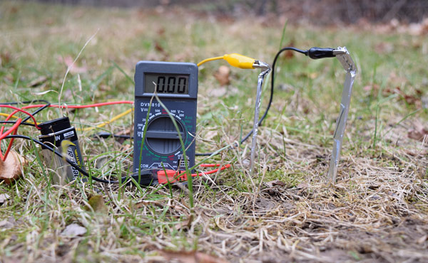 Leads of a multimeter attach to two aluminum foil props placed in the soil