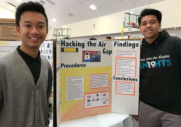 Two students standing in front of a science fair display board