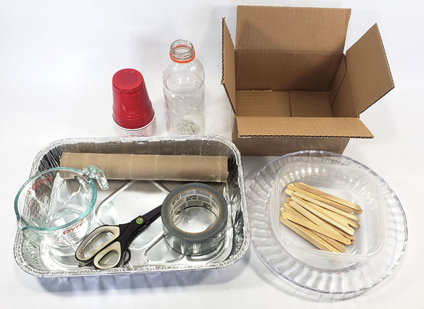 Plastic cups, a plastic bottle, a cardboard and tube, scissors, tape, popsicle sticks, a measuring cup and shallow containers