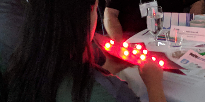 A woman holding a paper sheet covered in red LEDs