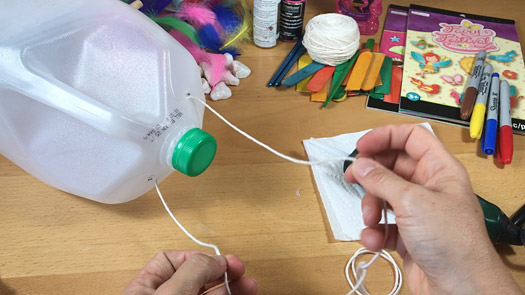 Yarn is threaded through holes in the top of the container to create a handle.