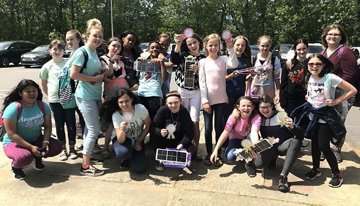 Students from an all-girl STEM club holding solar-powered cars