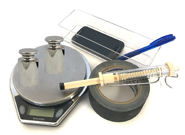 A scale, spring scale, plastic container, smartphone, tape and weights