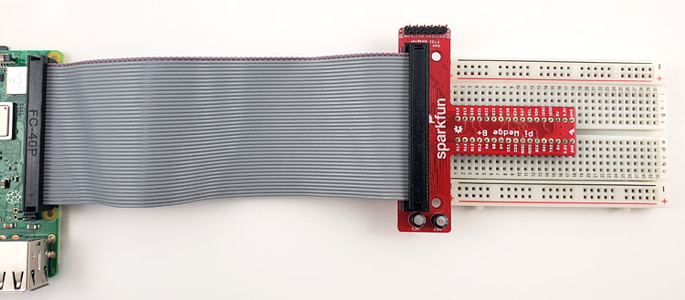 The Pi Wedge plugged into a breadboard and connected to the Raspberry Pi with a ribbon cable.