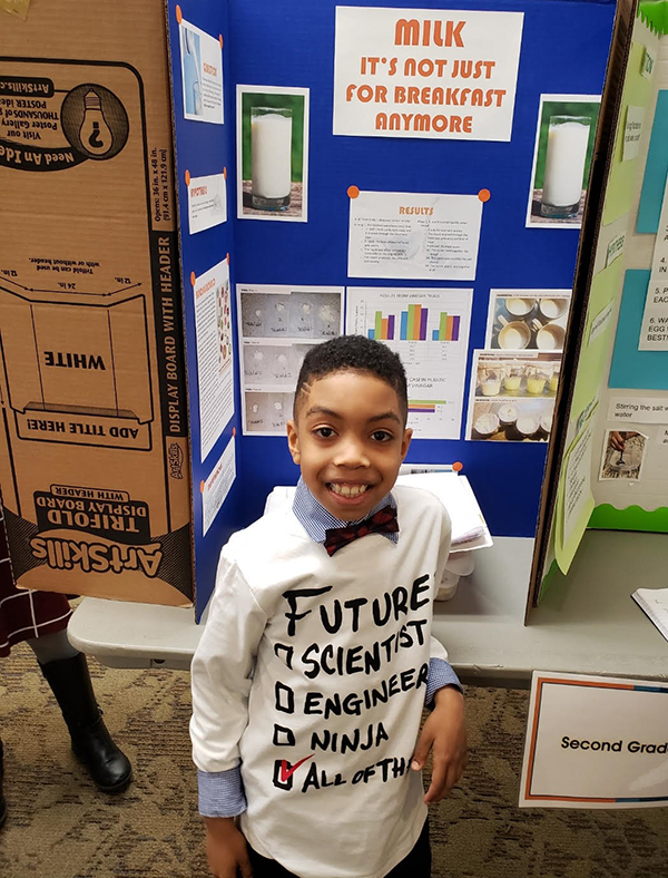 Student with his full second-grade project display board from the science fair.