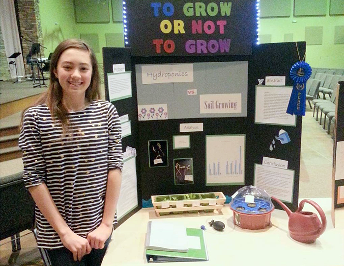 Student at science fair with hydroponics science project and display board