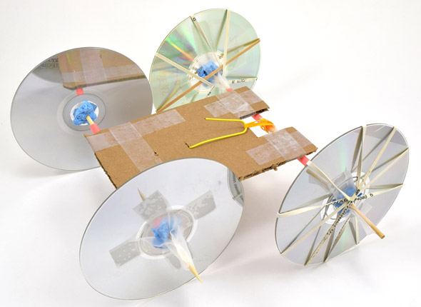 A homemade rubber band powered car made from CDs, cardboard, paperclips, tape, wooden skewers and rubber bands