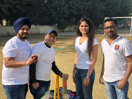 Three male and one female engineer dressed casually standing around cricket equipment on a sports field.