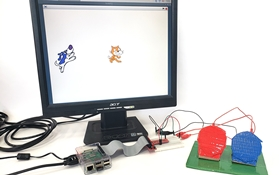 A raspberry pi, computer monitor showing Scratch, and adaptive game controller with two large buttons