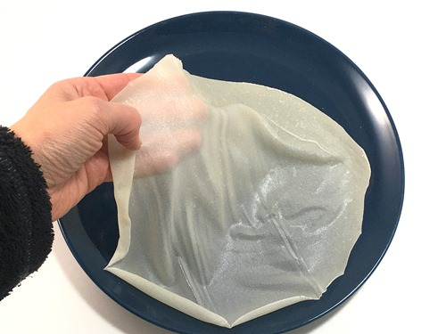 A hand placing a sheet of slightly translucent edible paper on a plate.
