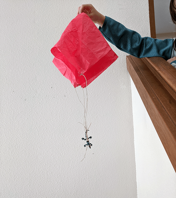 Student holding homemade parachute from the top of a stairwell landing and preparing to drop it to the bottom