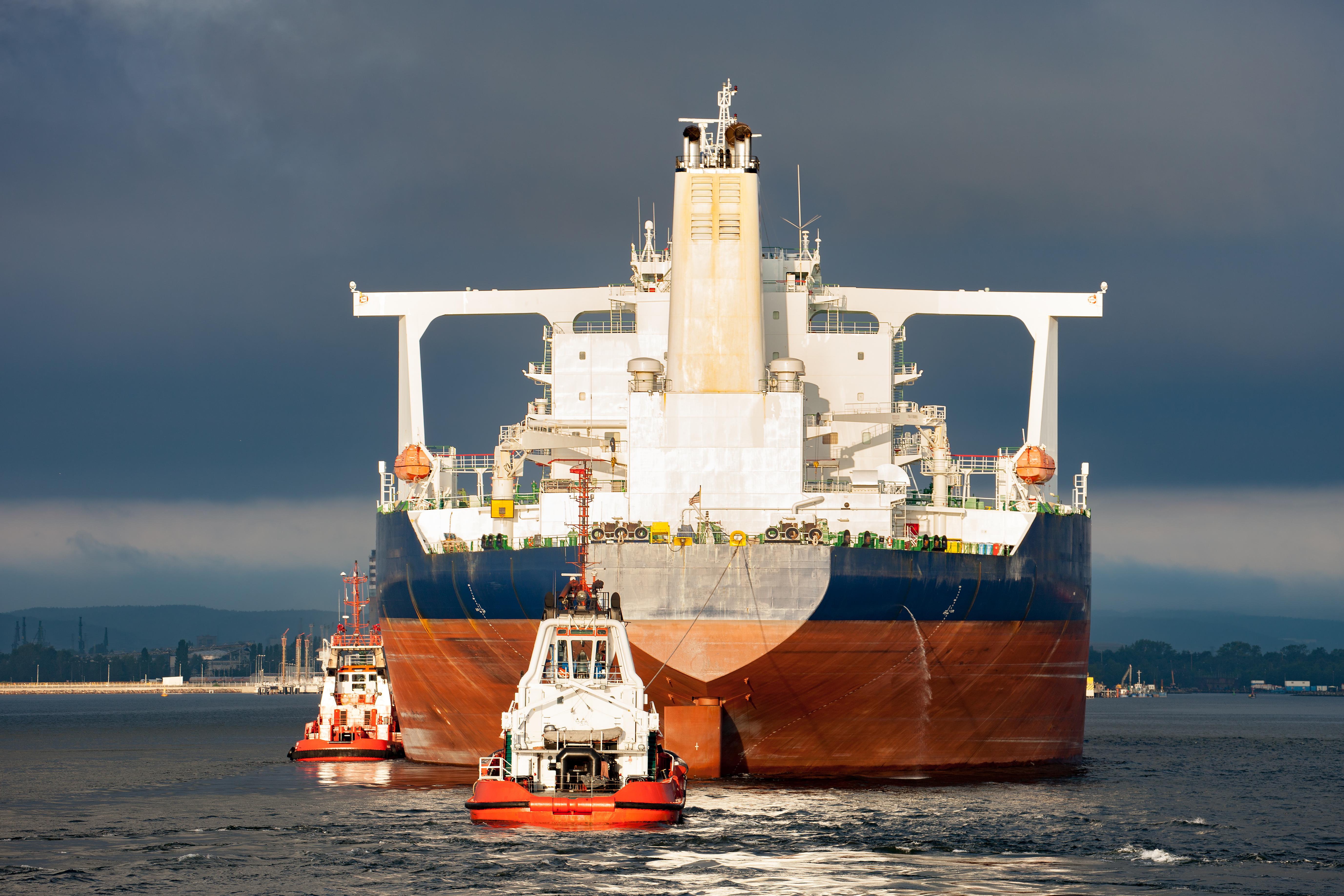 tugboat bringing ocean liner through canal