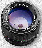 Photo of a camera lens where a small octagonal hole can be seen behind the glass of the lens