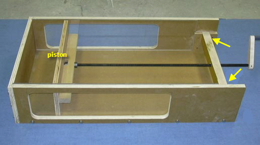 A shallow box is built with an open top and one side wall attached to a long screw