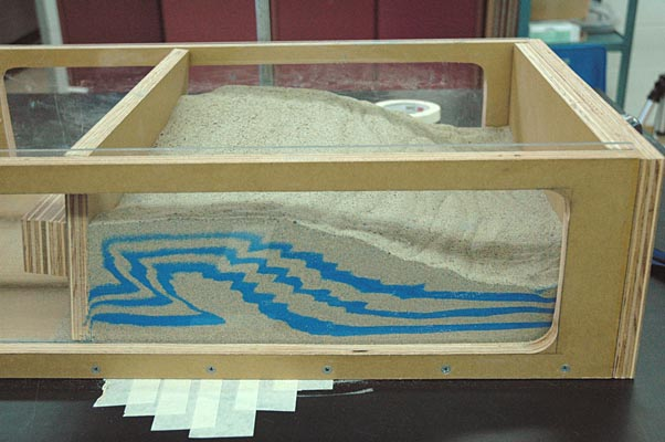 As a wood panel moves to compress sand, layers of blue sand are curved and bent