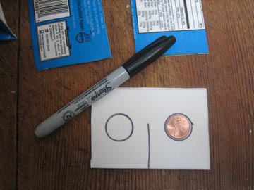 The shape of a penny is traced on the left and right side of a cardboard rectangle