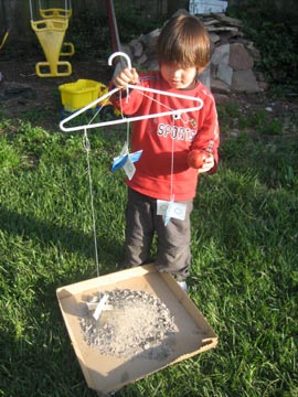 A child holds a clothes hanger with three homemade stardust catchers hanging from it